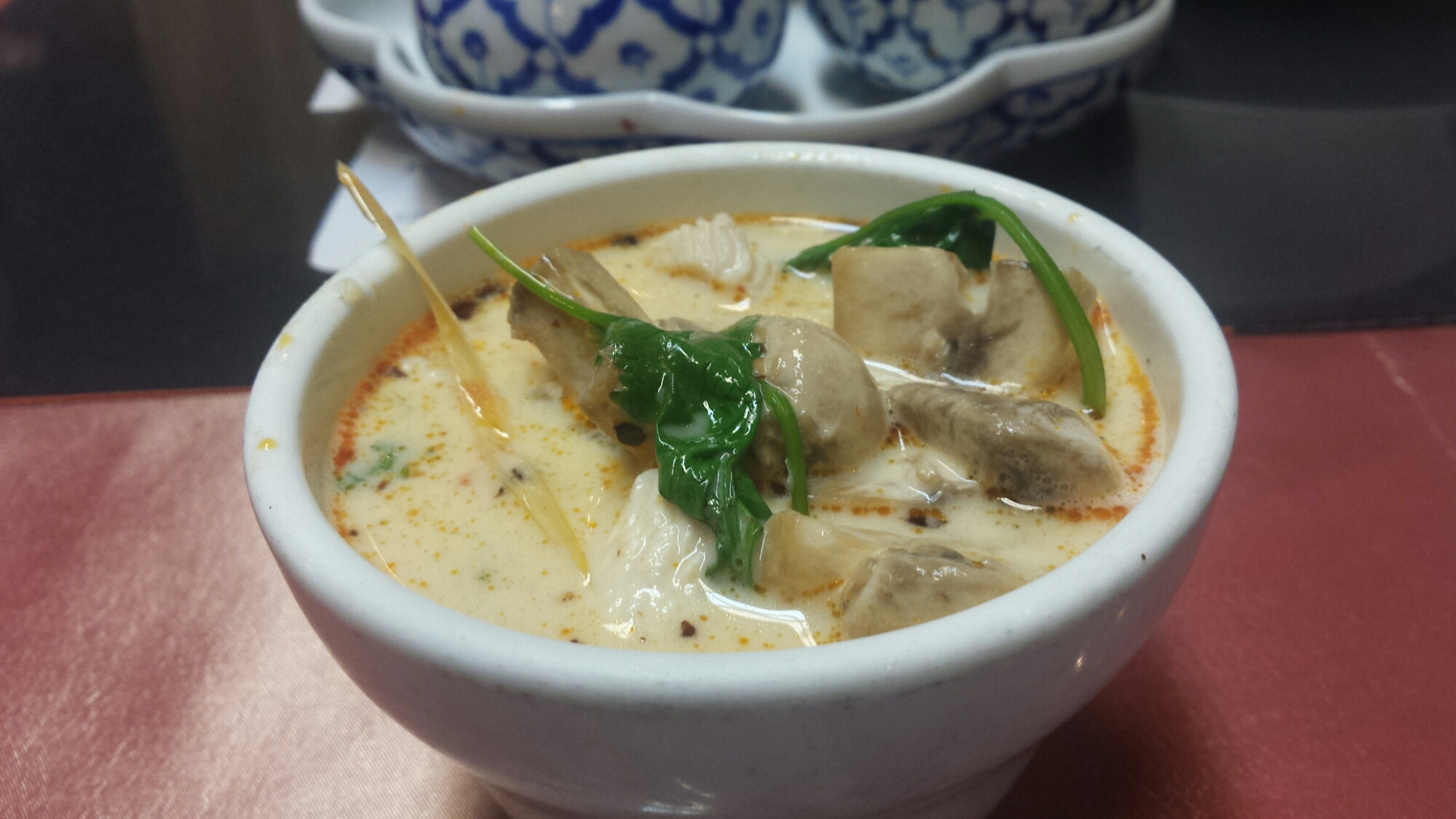 Tom Kha soup; spicy and sour soup in coconut milk, mushrooms, galangal, lemon grass and a touch of lime juice