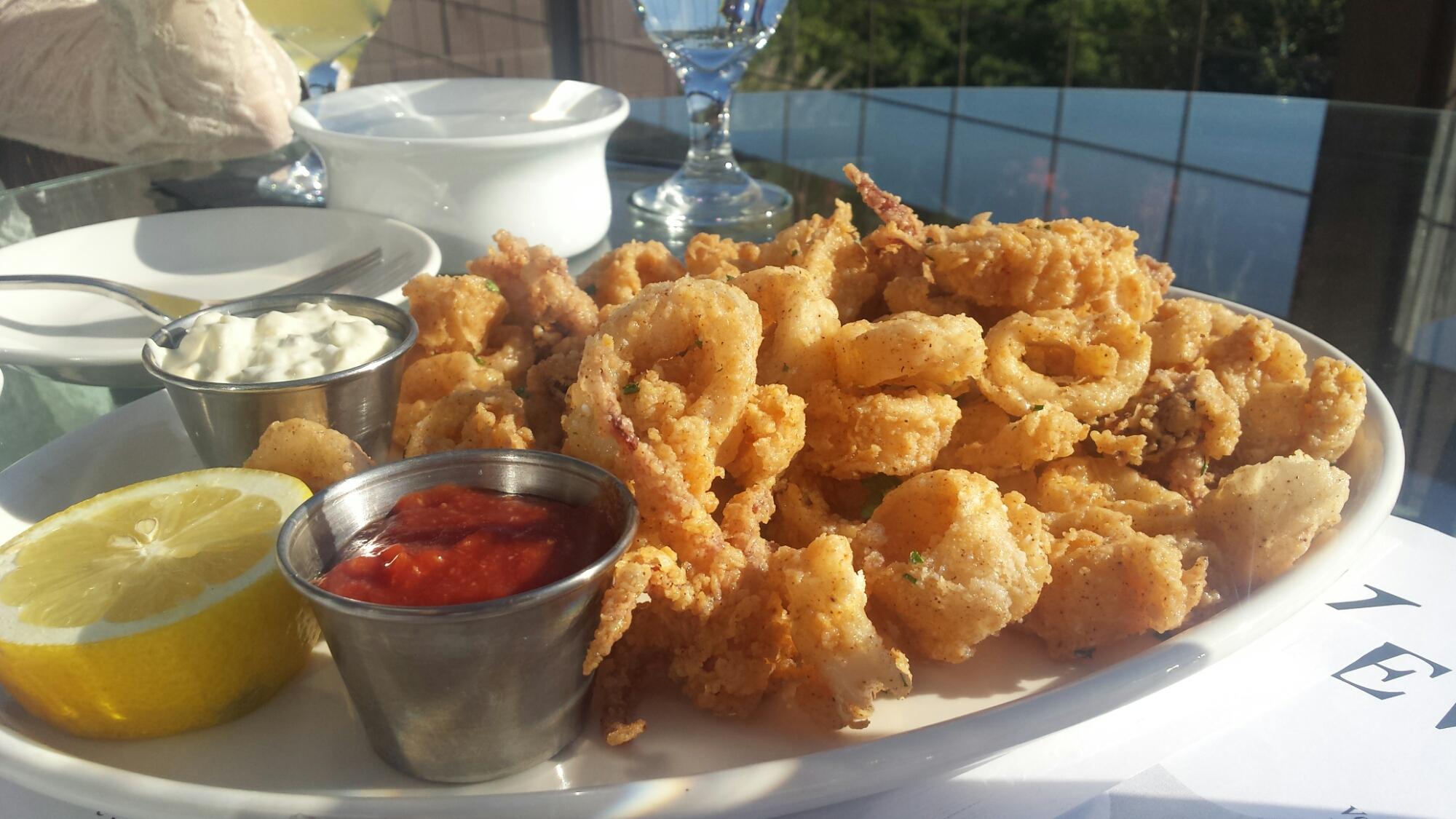 Calamari Fritti -local squid lightly floured, served with fresh lemon, and our signature cocktail and tartar sauces