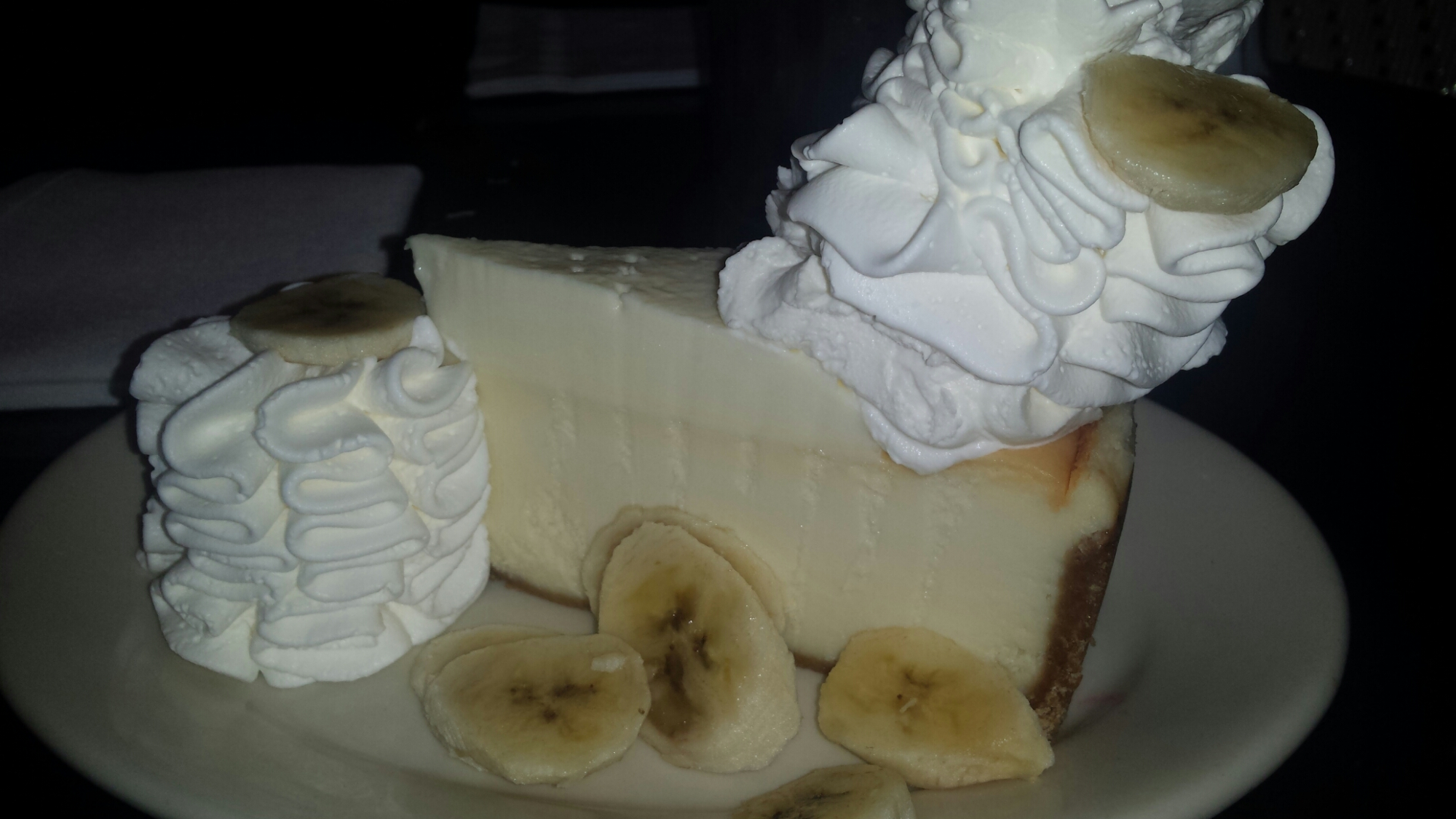 Banana Cream Cheesecake - Banana Cream Cheesecake Topped with Bavarian Cream and Fresh Sliced Bananas.