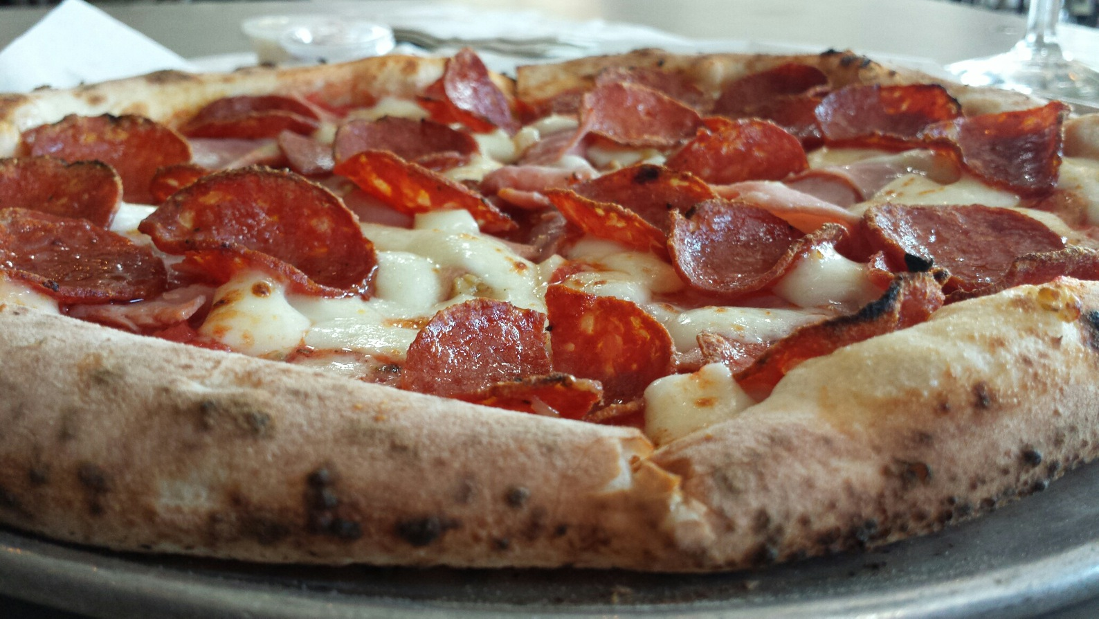 Patrizio Pizza which contains Pepperoni, Prosciutto Cotto, Roasted Garlic, Oregano, Chili Flakes, Mozzarella,Parmigiano Reggiano, and Crushed San Marzano Tomato Sauce .