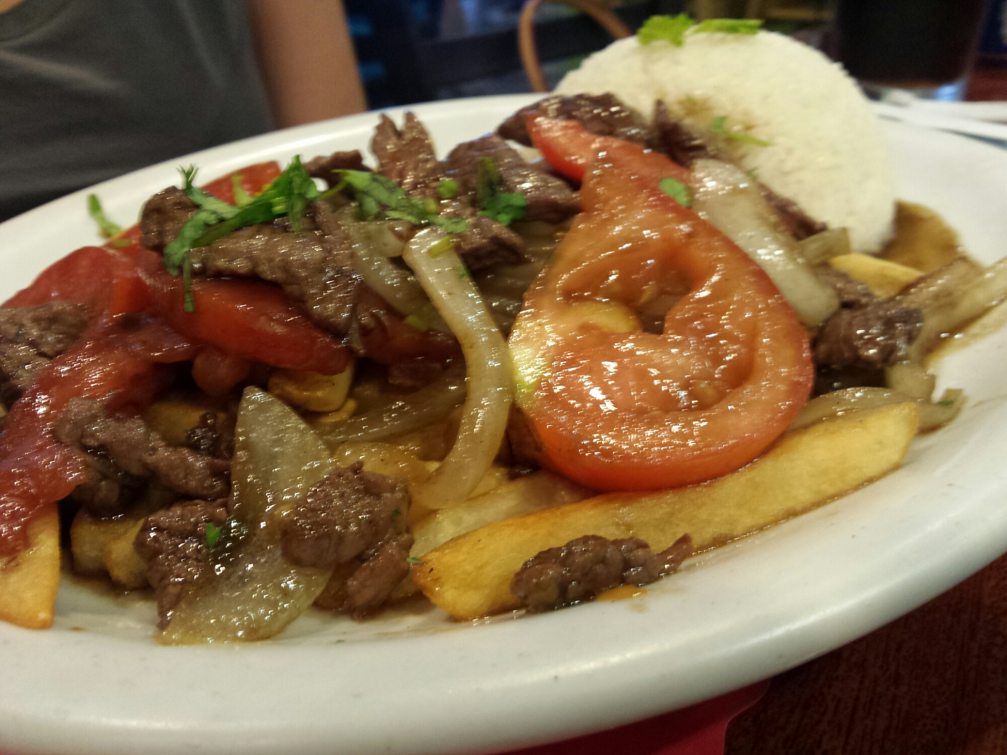 Lomo Saltado - Top sirloin strips sauteed with onions tomatoes, french fries and rice
